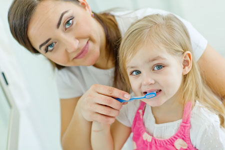 Mom and Daughter brushing their teeth - Pediatric Dentist in Plainfield, IL
